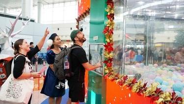 Hành khách nước ngoài thích thú với máy gắp quà tại sân bay Tân Sơn Nhất.