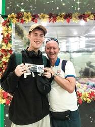 Ông Lachlan, du khách người Australia thích thú chụp ảnh kỷ niệm với voucher mua hàng vừa gắp được từ máy gắp quà.